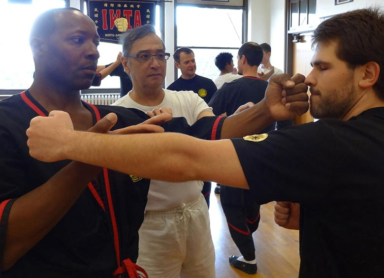 Photo: Great Grandmaster Leung Ting teaching authentic Wing Tsun kung fu during a visit to Dynamic Martial Arts of Bloomington-Normal. Sifu Darrell Taylor defends a punch from Sihing Sam Brucker using tan-da.