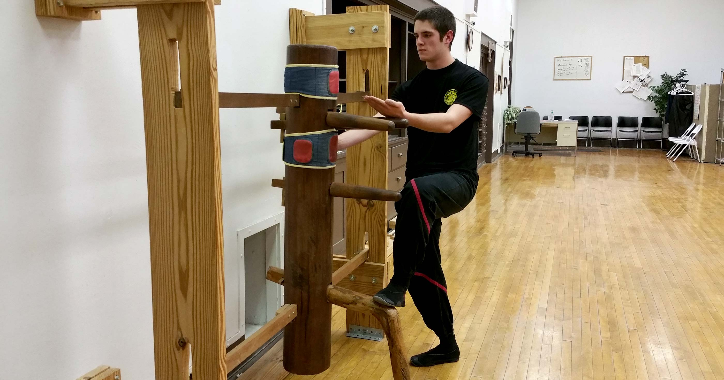Photo: Sifu Hunter Watts executes a WingTsun kung fu tan-sau with simultaneous lower lying palm and stamping kick on the wooden dummy.
