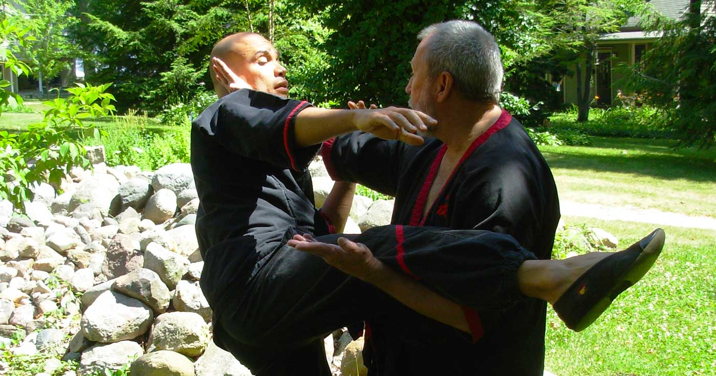 Photo: Master Mike Adams executes a WingTsun lau-sau (scooping hand) and fak-sau (whisking hand) to defend a roundhouse kick from Sifu Claudio Mascarenhas.